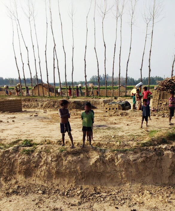 Malnourished children wait while their parents prepare to leave the Brick Kiln